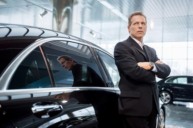 Rêver d'une nouvelle voiture. gentil homme aux cheveux gris en tenue de soirée se penchant sur la voiture et détournant les yeux