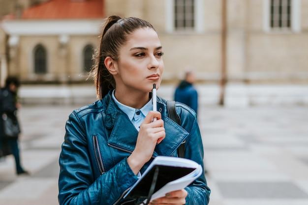 Rêverie jolie femme prenant des notes.