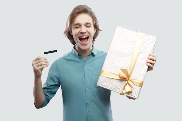 Les rêves deviennent réalité avec les achats en ligne ! jeune homme satisfait en chemise bleu clair debout et tenant un cadeau avec un arc jaune et une carte bancaire, les yeux fermés. intérieur, isolé, tourné en studio, fond gris