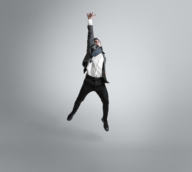 Rêves de grandes possibilités. un homme en tenue de bureau s'entraîne au football ou au football comme gardien de but sur un mur gris. look inhabituel pour homme d'affaires en mouvement, action. sport, mode de vie sain.