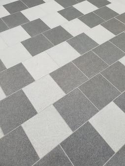 Un revêtement de sol en carreaux gris à deux nuances de motif aléatoire