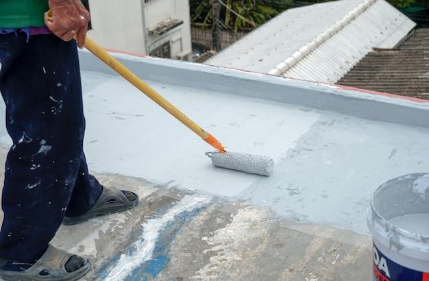 Revêtement de sol gris peint à la main avec rouleaux à peinture pour filet de renforcement imperméableréparation de l'imperméabilisation