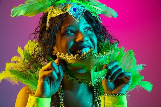 Rêveur. belle jeune femme en carnaval, costume de mascarade élégant avec des plumes dansant sur un mur dégradé en néon. concept de célébration de vacances, temps festif, danse, fête, s'amuser.