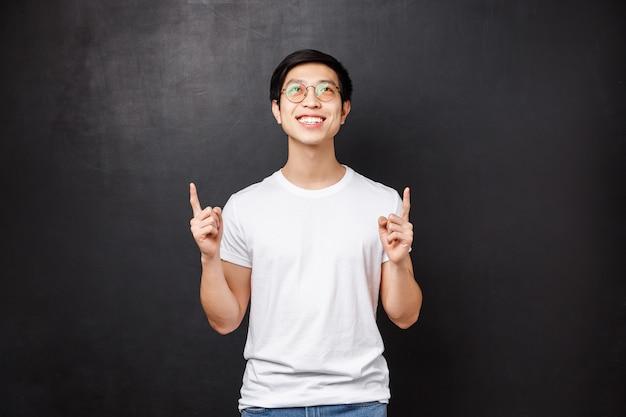 Rêveur heureux homme asiatique souriant regardant et pointant vers le haut, voir la meilleure annonce avec bonne affaire, décider d'essayer lui-même, contemplant une belle chose, debout mur noir