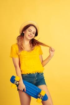 Rêveur, tient le patin. portrait de femme caucasienne sur fond de studio jaune. beau modèle féminin au chapeau. concept d'émotions humaines, expression faciale, ventes, publicité. l'été, les voyages, la station balnéaire.
