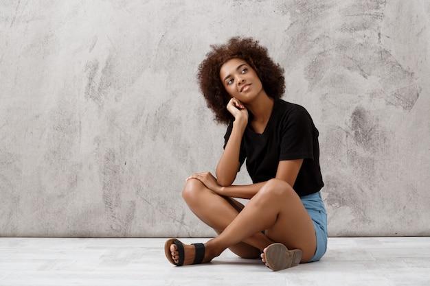 Rêveuse belle fille africaine assise et souriant sur le mur lumineux.