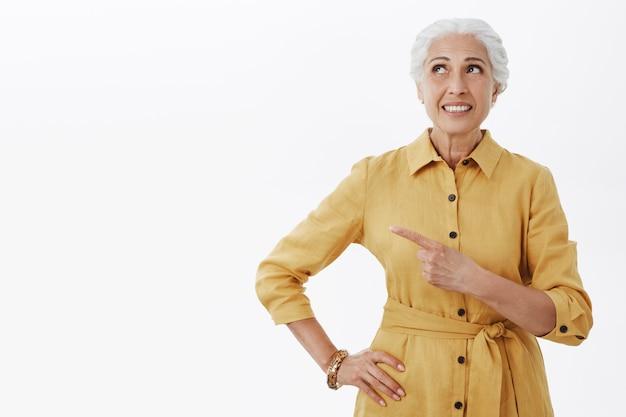Rêveuse femme âgée souriante regardant et pointant le coin supérieur gauche