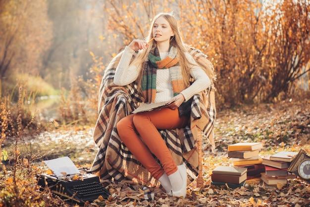 Rêveuse femme écrivant dans le parc en automne