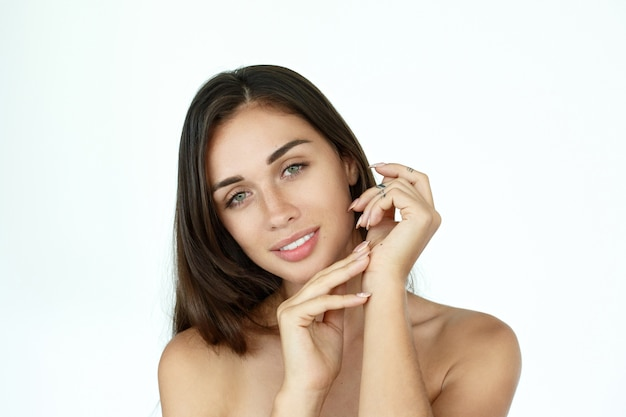 Rêveuse femme touche son visage tendre debout sur fond blanc