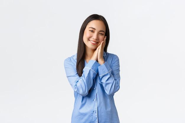 Rêveuse fille asiatique souriante en pyjama bleu se prépare à dormir, le visage appuyé sur les paumes et souriant comme