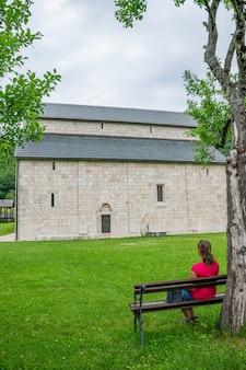 Rêveuse fille solitaire est assise sur un banc près du monastère.