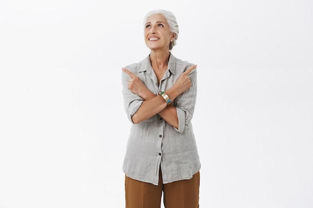 Rêveuse mamie souriante pointant les doigts sur le côté, faisant un choix, regardant le coin supérieur gauche