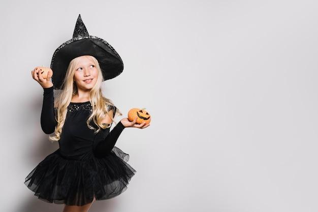 Rêveuse petite sorcière avec des citrouilles
