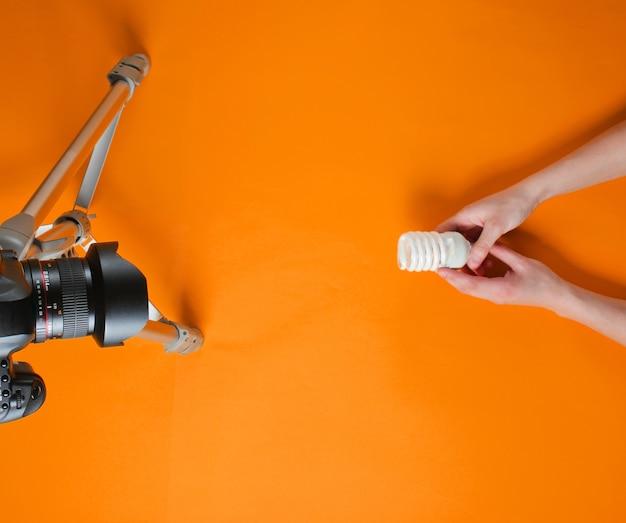 Revue de main de femmes ampoule spirale eco avec appareil photo sur trépied sur fond orange. vue de dessus. minimalisme