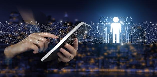 Rh ressources humaines recrutement emploi. tablette blanche tactile à la main avec hologramme numérique humain, signe de leader sur fond flou sombre de la ville. concept de gestion des ressources humaines et de l'équipe.