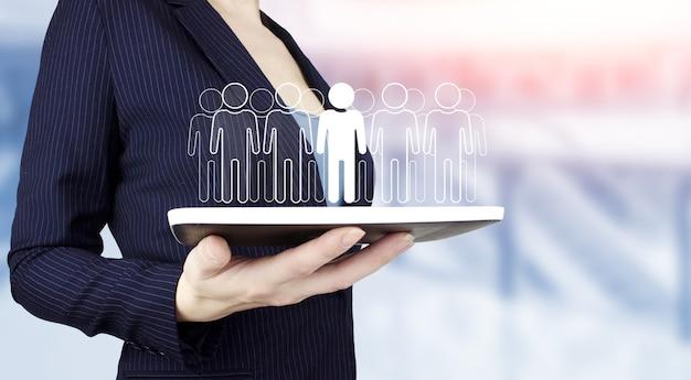Rh ressources humaines, structure organisationnelle des relations humaines. tenir à la main une tablette blanche avec hologramme numérique humain, signe de leader sur fond flou clair. communauté, unité, personnes et soutien.