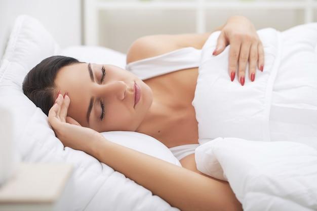Rhume et grippe. la femme dort et tient sa tête avec un stress subliminal ou d'autres symptômes possibles