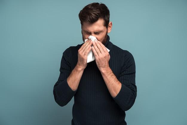Rhume et grippe. portrait d'un jeune homme barbu malade debout, tenant un mouchoir sur la bouche et ressentant de la tristesse et de la maladie. studio intérieur tourné, isolé sur fond bleu