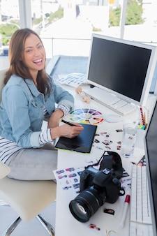 Riant éditeur de photos travaillant avec une tablette graphique