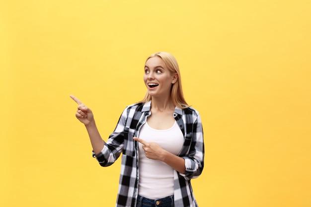 Riant jeune femme en t-shirt à la recherche et pointant loin avec le pouce sur fond jaune