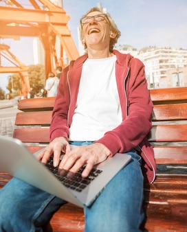 Riant senior homme assis sur un banc avec un ordinateur portable ouvert sur ses genoux