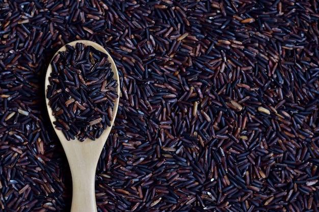 Riceberry (baie de riz) qui est une variété de riz enregistrée de thaïlande dans une cuillère en bois