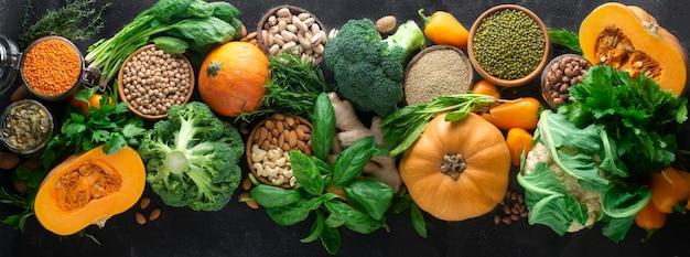 Un riche assortiment de légumes d'automne de saison, céréales et noix: brocoli, chou-fleur, potiron, épinards, basilic, persil, gingembre, haricot mungo, quinoa, haricots, noix de cajou, amandes, pistaches. bannière