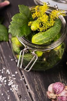 Riche récolte de concombres biologiques frais prêts à être conservés dans un bocal en verre.