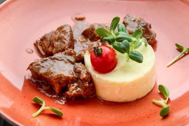 Riche et savoureux bœuf bourguignon avec purée de pommes de terre sur une plaque sur une surface en bois