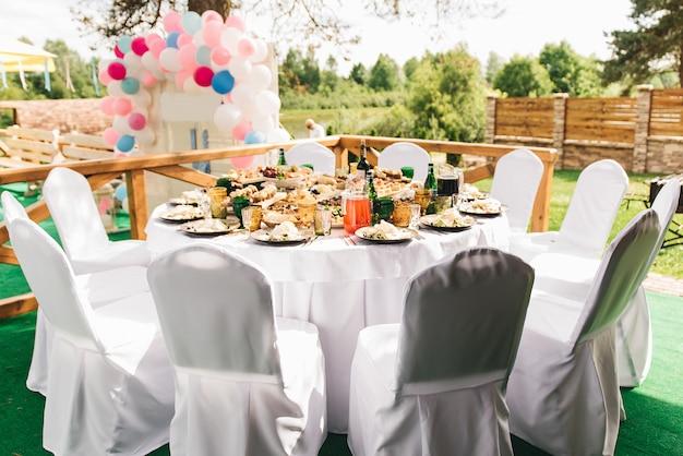 La riche table ronde festive avec nappe et chaises blanches, servie avec une variété de plats et de boissons, se dresse sur l'herbe verte dans la zone de banquet de mariage contre le manoir en bois