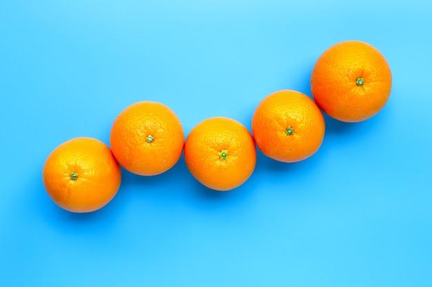 Riche en vitamine c, fruit orange frais juteux et sucré sur fond bleu