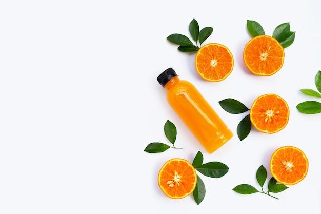 Riche en vitamine c, juteuse et sucrée. fruits orange frais avec une bouteille de jus d'orange sur fond blanc. copier l'espace
