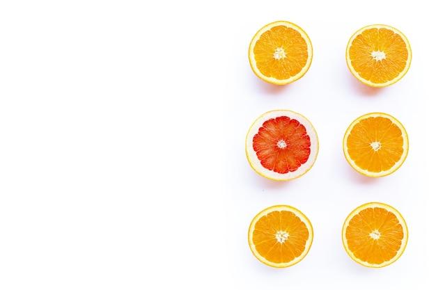 Riche en vitamine c, juteuse et sucrée. orange fraîche et pamplemousse sur une surface blanche.