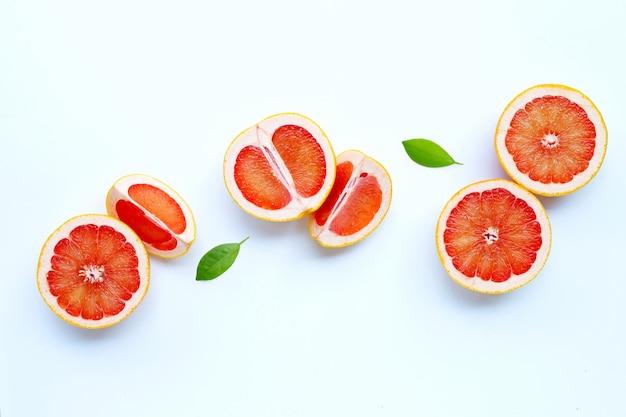 Riche en vitamine c. pamplemousse juteux avec des feuilles sur blanc.