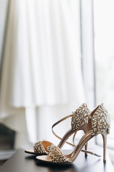 De riches chaussures scintillantes avec des cristaux se tiennent devant une robe suspendue