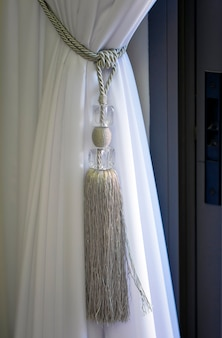 Rideau blanc drapé noué avec une grande corde à tisser. intérieur du rideau à rayons du salon noué avec une attache de luxe, corde dans le salon. fenêtre avec de belles attaches décoratives en textiles pour rideaux
