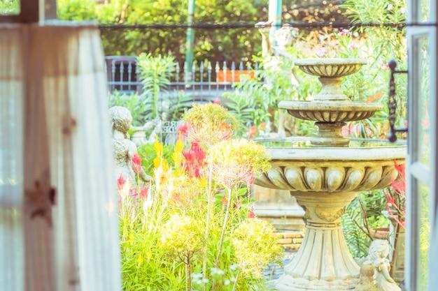 Rideau blanc fait main avec vue sur la fenêtre de la fontaine et du vert du fond du jardin arboré