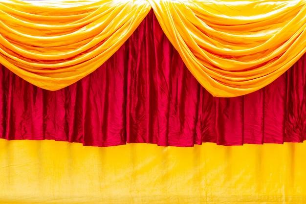 Rideau de théâtre de scène rouge et jaune en arrière-plan.