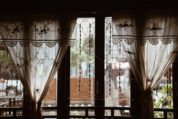 Rideau en tissu de coton au crochet fait main beige près de la fenêtre en verre
