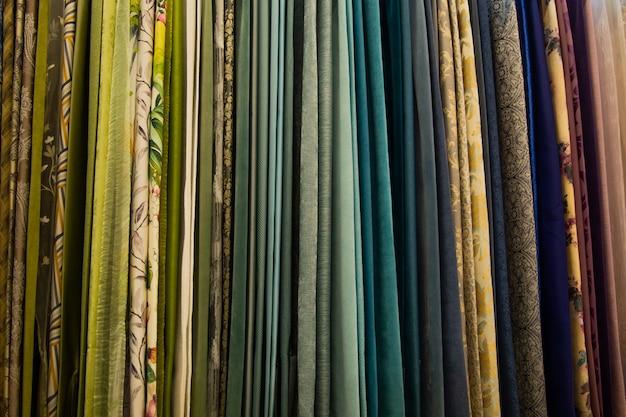 Des rideaux de différentes couleurs et motifs pour la pièce sont suspendus horizontalement. photo de haute qualité