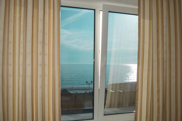 Rideaux à la fenêtre, vue mer au coucher du soleil, chemin argenté, soirée d'été.