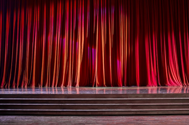 Rideaux rouges et scène en bois.
