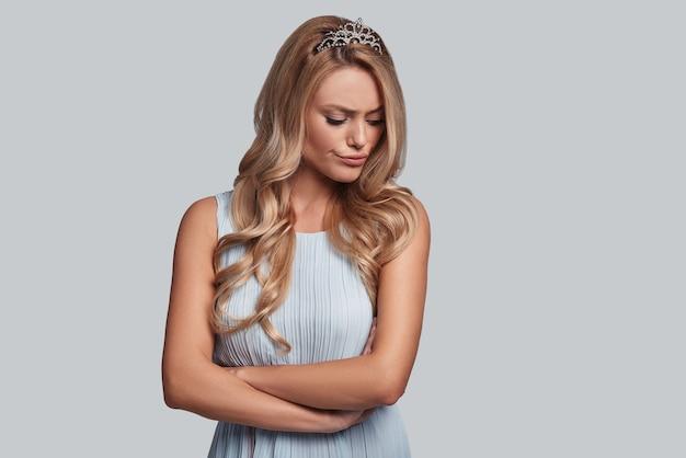 Rien ne la réconforte. jeune femme fière en couronne gardant les bras croisés et faisant une grimace en se tenant debout sur fond gris