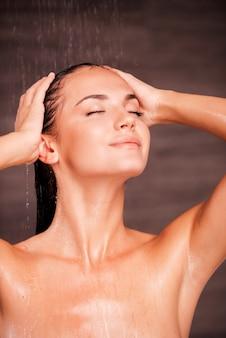 Rien de tel qu'une douche chaude. belle jeune femme torse nu debout dans la douche et se laver les cheveux