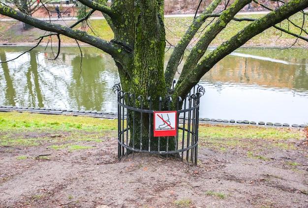 Riga, lettonie - 5 décembre 2018 : clôture de garde d'arbre près de l'arbre dans le parc à riga. signe interdit de marcher.