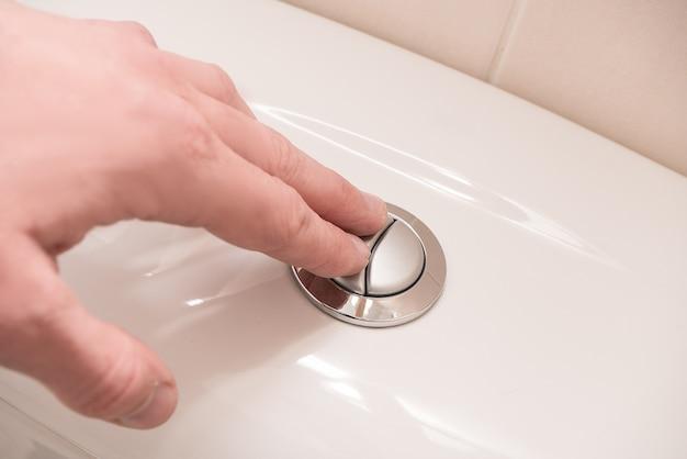 Rinçage des toilettes. main sur le bouton.