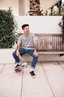 Rire adolescent assis sur un banc en bois en plaçant le pied sur la planche à roulettes