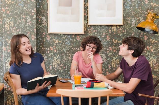 Rire des adolescents qui étudient au café