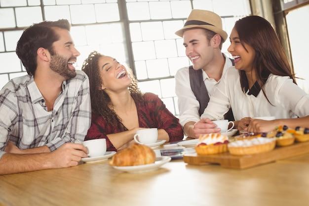 Rire des amis en appréciant le café et les friandises