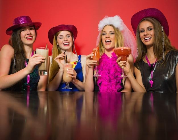 Rire des amis ayant une fête de poule tenant des cocktails